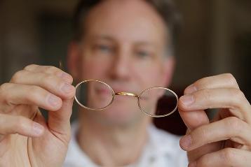 Dr Sylvester M Maas zeigt seine Brille